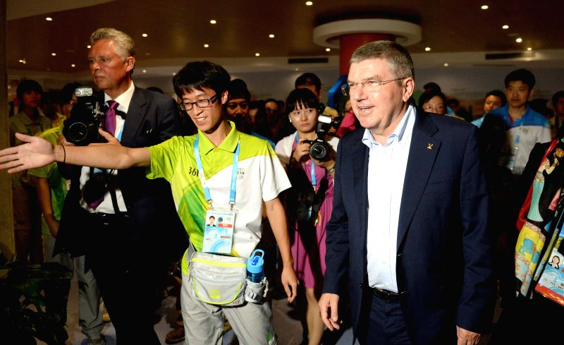 International Olympic Committee President Thomas Bach (front, R) visits the Main Media Centre of the Nanjing 2014 Youth Olympic Games in Nanjing, capital of east ..
