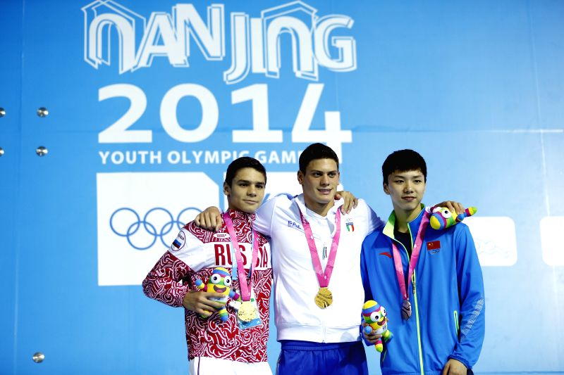 Gold medalist Evgeny Rylov of Russia and Simone Sabbioni of Italy,bronze medalist Li Guangyuan of China pose for a photo on the podium during the awarding ceremony .
