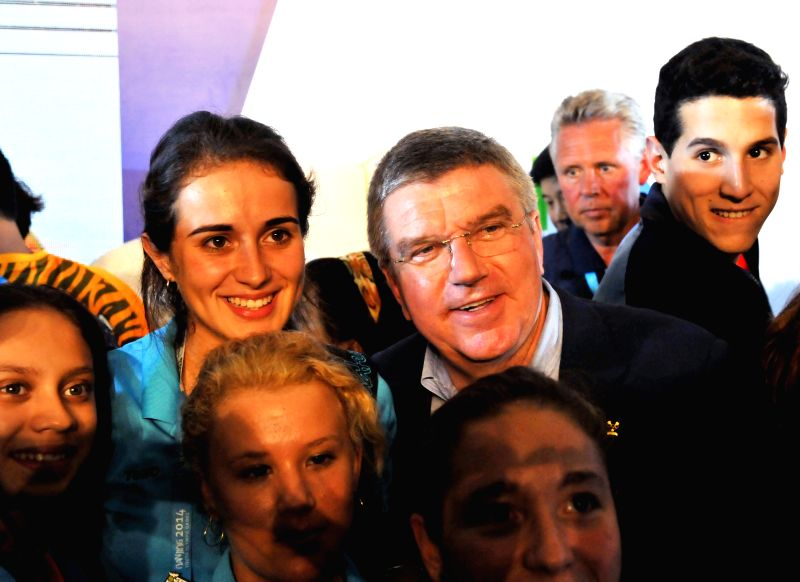 "The President of the International Olympic Committee Thomas Bach (R, 2nd Row) poses for photos with young athletes during an activity  ""Conversation with ..."