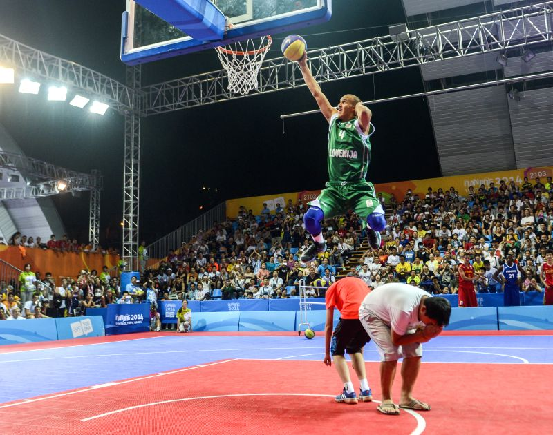 Silver medalist Ziga Lah (T) of Slovenia competes during men's dunk contest final of basketball at the Nanjing 2014  Youth Olympic Games in Nanjing, east China's ...