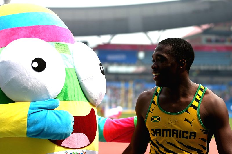 Gold Medalist Martin Manley is greeted by LELE, the mascot of YOG, after the men`s 400m Final of athletics event of athletics event at the Nanjing 2014 Youth ...