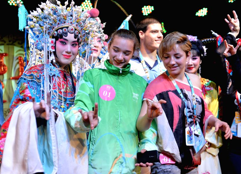 Athletes learn a hand pose with an actress during a visit to Jinling Theater at Laomendong, Nanjing, capital city of east China's Jiangsu Province, August 24, 2014.