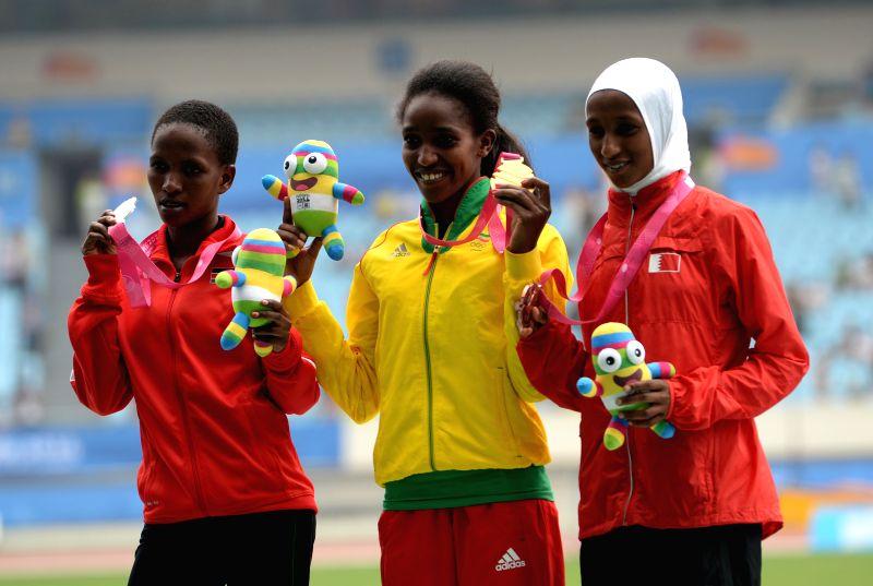 Gold medalist Kokeb Tesfaye Alemu (C) of Ethiopia, silver medalist Winfred Mbithe (L) of Kenya, bronze medalist Dalila Gosa of Bahrain pos on the podium during the