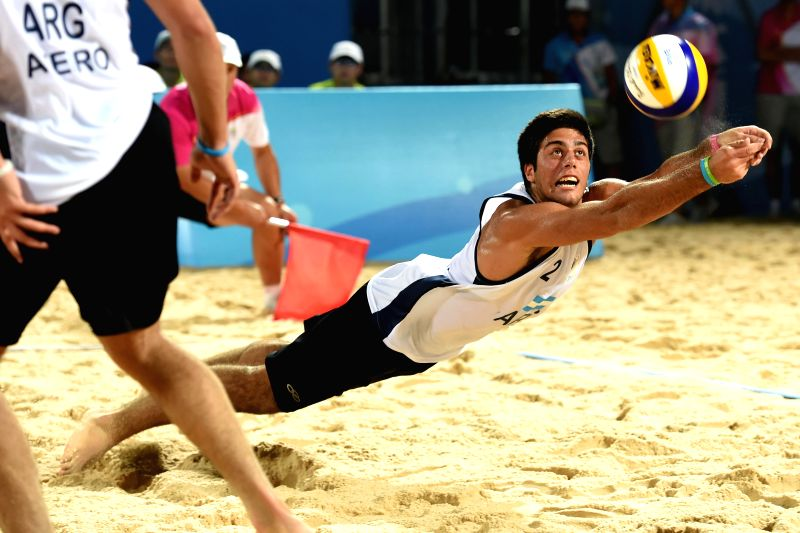 Santiago Karim Aulisi of Argentina saves the ball during the men's quarterfinal match of beach volleyball event against Germany at the Nanjing 2014 Youth Olympic ...