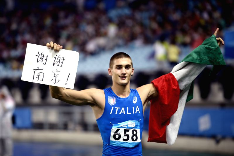 Silver medalist Tobia Bocchi of Italy celebrates by lifting the board reading Thanks Nanjing after men's triple jump at the Nanjing 2014 Youth Olympic Games in ...