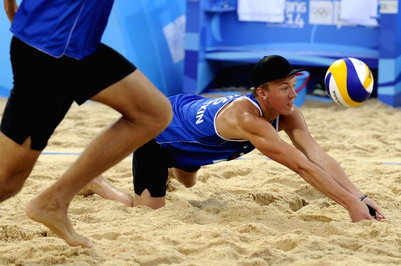 Artem Iarzutkin (R) of Russian Federation competes during the men's semifinal of beach volleyball competition against Finland at Nanjing 2014 Youth Olympic Games in