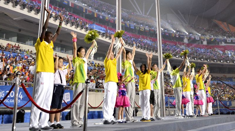 Representatives of volunteers  receive bouquets during the closing ceremony of Nanjing 2014 Youth Olympic Games in Nanjing, capital of east China?s Jiangsu ...