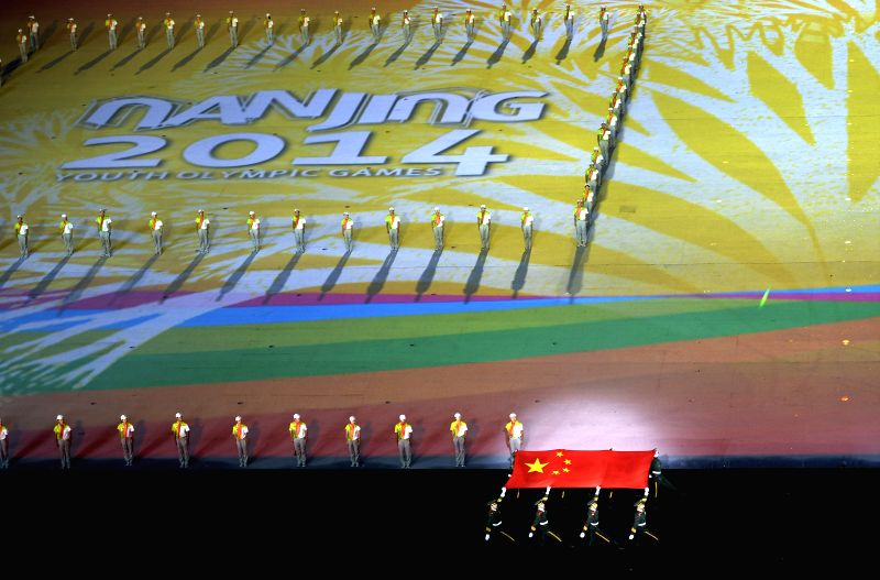 The national flag of People`s Republic of China enters the stadium during the closing ceremony of Nanjing 2014 Youth Olympic Games in Nanjing, capital of east ...