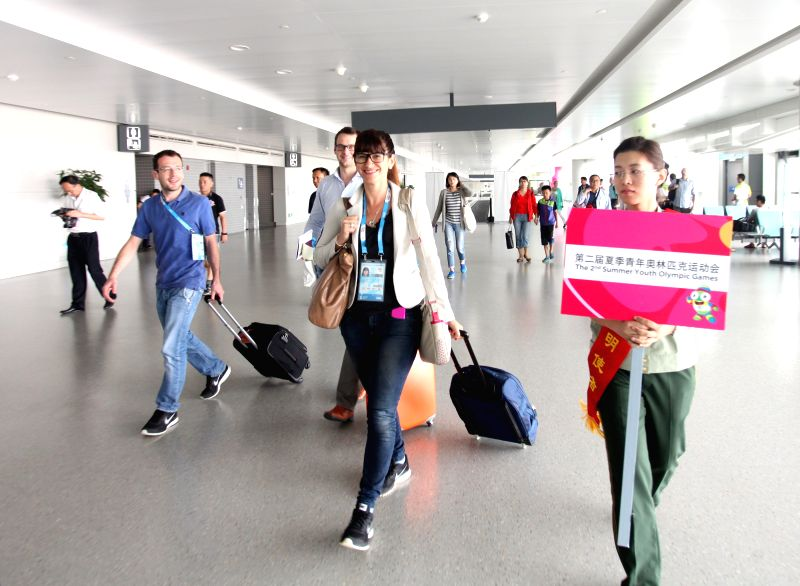 A guide leads officials of the Youth Olympic Games Organizing Committee at Lukou International Airport in Nanjing, capital of east China's Jiangsu Province, Aug. 6, .