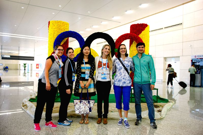 Officials of the Youth Olympic Games Organizing Committee pose for group photos at Lukou International Airport in Nanjing, capital of east China's Jiangsu Province, ..
