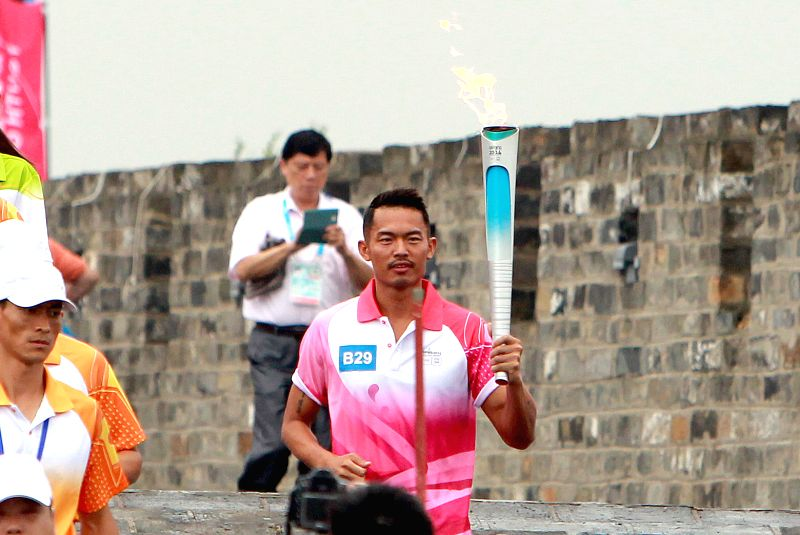 Chinese famous badminton player Lin Dan runs with the Olympic torch on the city wall during the Olympic Torch Relay for the Nanjing Youth Olympic Games in Nanjing, ..