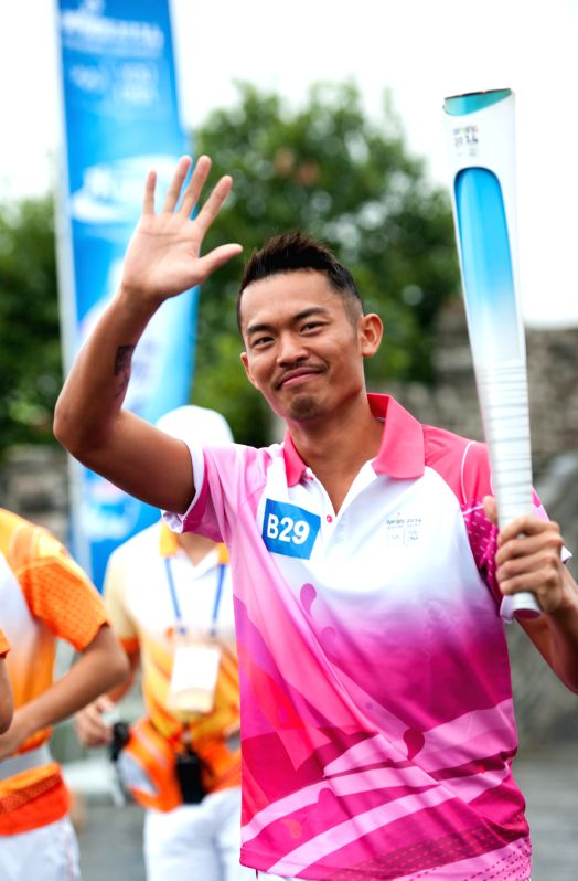 Chinese famous badminton player Lin Dan waves during the Olympic Torch Relay for the Nanjing Youth Olympic Games in Nanjing, capital of east China's Jiangsu ...