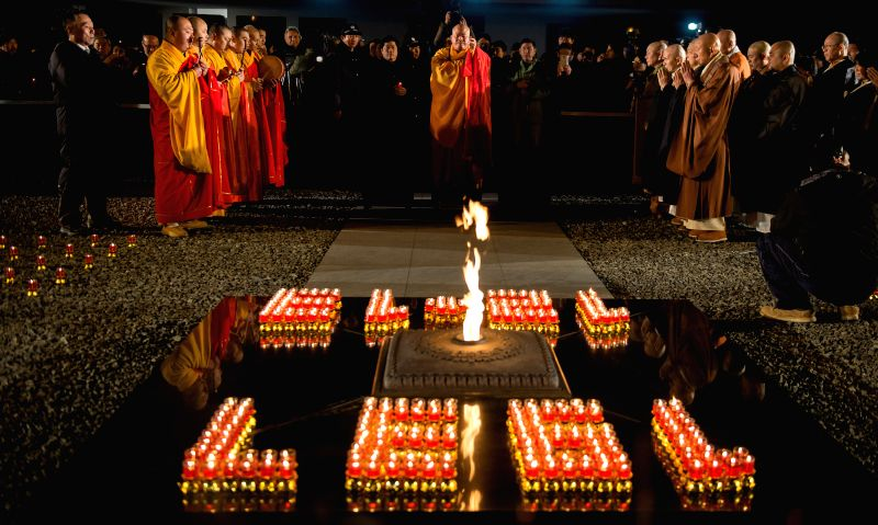 Monks pray for the victims of Nanjing Massacre during China's first National Memorial Day for Nanjing Massacre Victims in Nanjing, east China's Jiangsu Province, ...