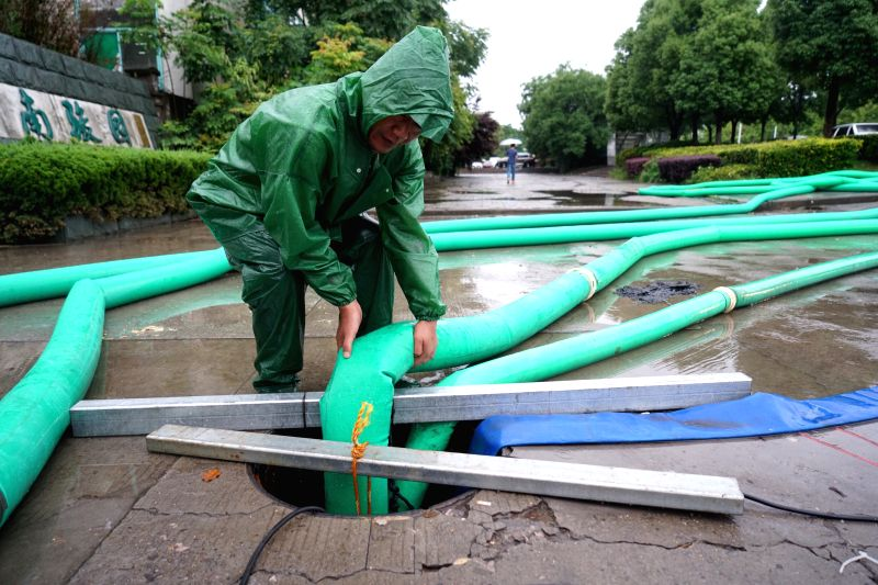"NANJING, June 10, 2017 - A drainage worker works on a street in Nanjing, capital of east China's Jiangsu Province, June 10, 2017. Nanjing on Saturday upgraded its ""heavy rain"" alert to red, ..."