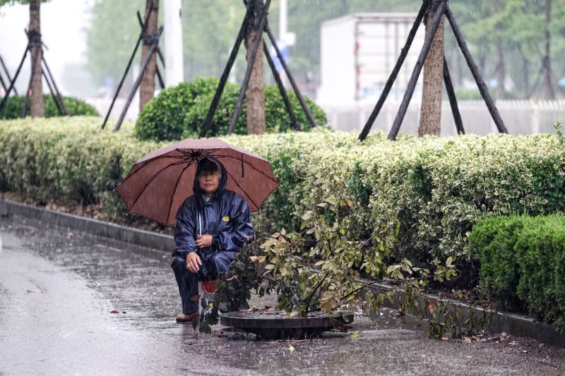 "NANJING, June 10, 2017 - A staff member guards a drainage pipe on a street in Nanjing, capital of east China's Jiangsu Province, June 10, 2017. Nanjing on Saturday upgraded its ""heavy rain"" ..."
