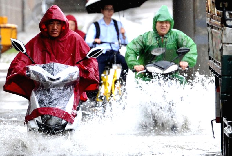 "NANJING, June 10, 2017 - Citizens ride on a flooded street in Nanjing, capital of east China's Jiangsu Province, June 10, 2017. Nanjing on Saturday upgraded its ""heavy rain"" alert to red, ..."