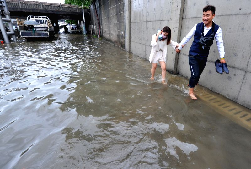 "NANJING, June 10, 2017 - Citizens walk on a flooded street in Nanjing, capital of east China's Jiangsu Province, June 10, 2017. Nanjing on Saturday upgraded its ""heavy rain"" alert to red, ..."