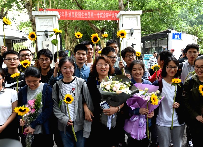 NANJING, June 10, 2018 - Examinees pose for a group photo with their teacher outside an exam venue at a middle school in Nanjing, capital of east China's Jiangsu Province, June 9, 2018. The national ...