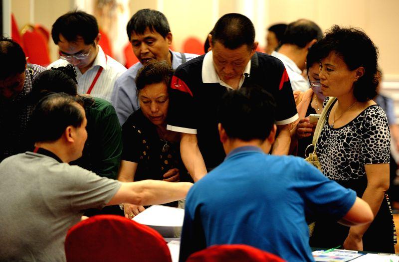 Staff members of the Nanjing Tourism Bureau help passenger relatives fill in a registration form in Nanjing, capital of east China's Jiangsu Province, June 2, 2015. ...