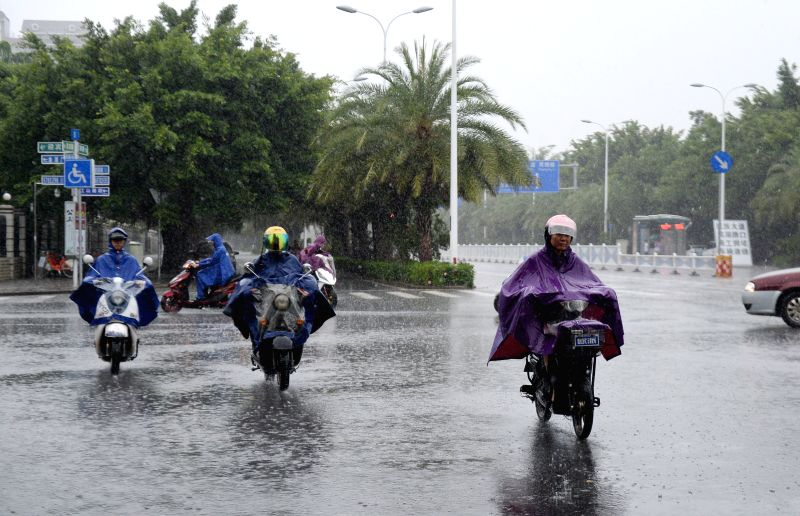 NANNING, July 28, 2016 - People ride against rain on the Binhu Road in Nanning, capital of south China's Guangxi Zhuang Autonomous Region, July 28, 2016. Local meteorologic authority issued an orange ...