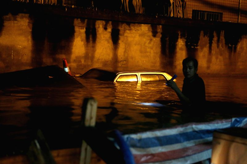 NANNING, June 4, 2016 - A resident checks his car almost submerged in water on Jianzheng East Road in Nanning, capital of south China's Guangxi Zhuang Autonomous Region, June 4, 2016. Some areas of ...