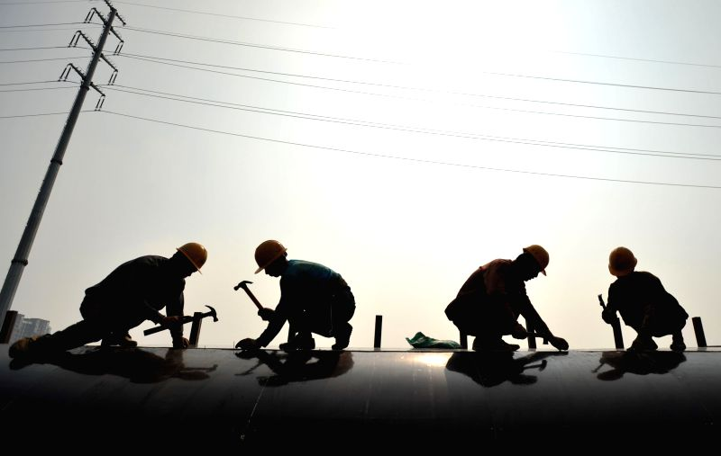 People work at an overpass construction site in Nanning, capital of southwest China's Guangxi Zhuang Autonomous Region, May 1, 2014.