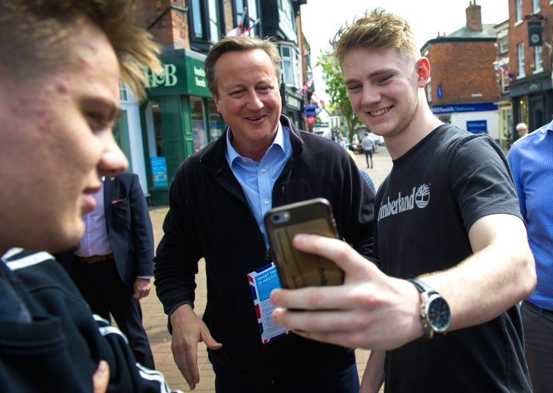 NANTWICH (BRITAIN), May 11, 2017 Former British Prime Minister David Cameron (C) stops for a selfie with a young man while campaigning for Conservative Party in Nantwich, Britain on May ... - David Cameron