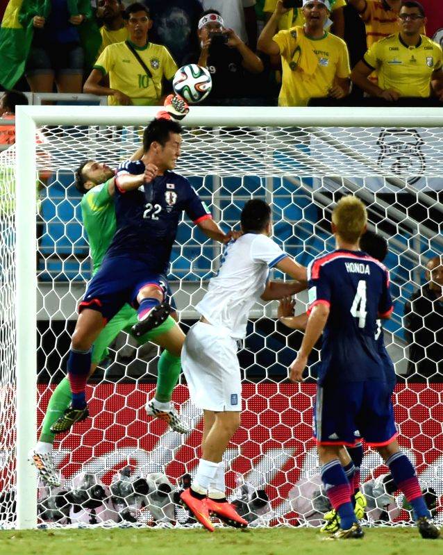 Japan's Maya Yoshida (2nd L) competes for a header during a Group C match between Japan and Greece of 2014 FIFA World Cup at the Estadio das Dunas Stadium in Natal, ..