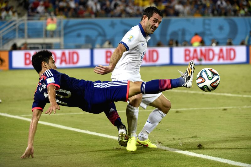 Japan's Shinji Kagawa (L) competes for the ball with Greece's Giorgos Karagounis during a Group C match between Japan and Greece of 2014 FIFA World Cup at the Estadio