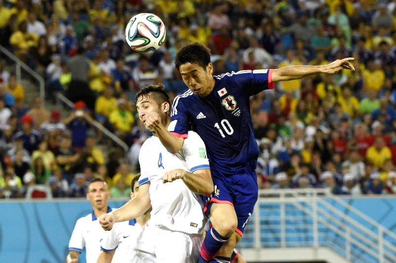 Japan's Shinji Kagawa (R) competes for a header with Greece's Kostas Manolas during a Group C match between Japan and Greece of 2014 FIFA World Cup at the Estadio das