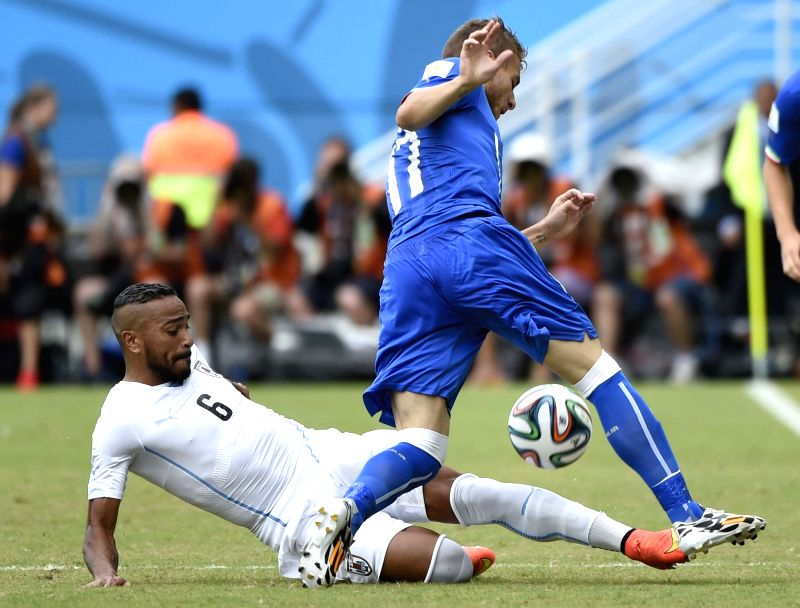 Italy's Ciro Immobile vies with Uruguay's Alvaro Pereira during a Group D match between Italy and Uruguay of 2014 FIFA World Cup at the Estadio das Dunas Stadium in ..
