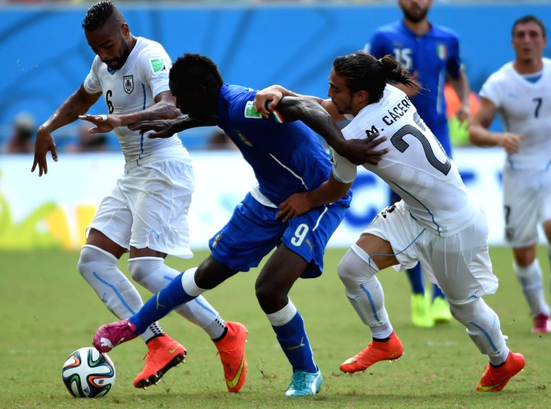 Italy's Mario Balotelli (C) vies for the ball during a Group D match between Italy and Uruguay of 2014 FIFA World Cup at the Estadio das Dunas Stadium in Natal, Brazil, .