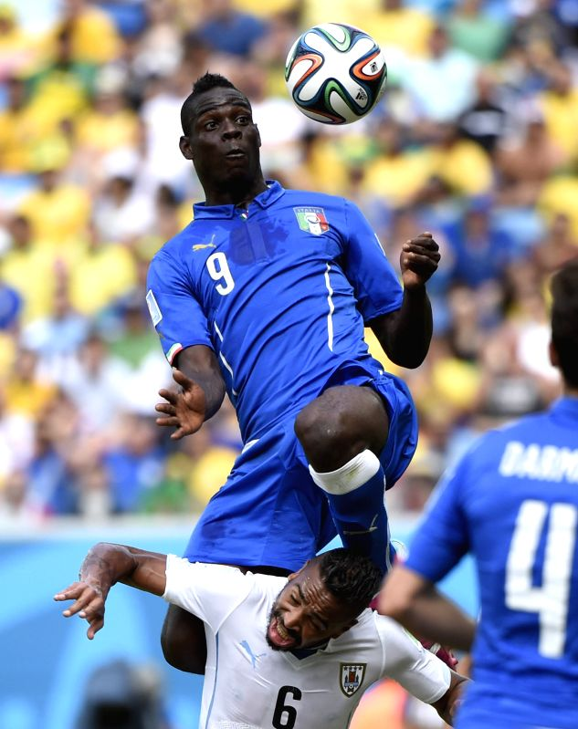 (Italy's Mario Balotelli (up) jumps for the ball during a Group D match between Italy and Uruguay of 2014 FIFA World Cup at the Estadio das Dunas Stadium in Natal, ...