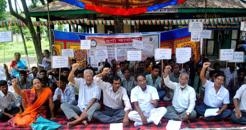 Nationalist Congress Party (NCP) workers stage a sit-in demonstration against water-logging in Guwahati on July 10, 2014.