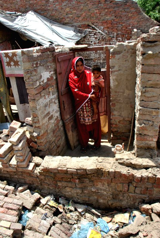 A woman with her child stands at the entrance of her damaged house in earthquake hit area of southern Pakistan's Nawabshah, May 9, 2014. At least two people were ...