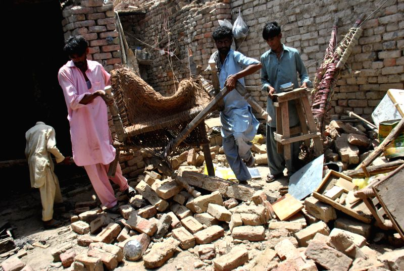 People remove debris from a destroyed house in earthquake hit area of southern Pakistan's Nawabshah, May 9, 2014. At least two people were killed and 40 others ...