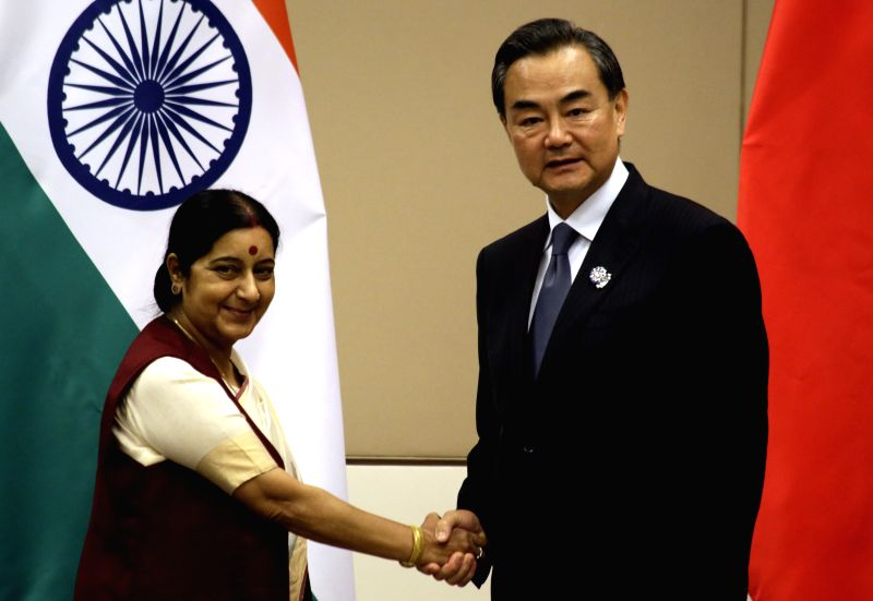 Chinese Foreign Minister Wang Yi (R) meets with Indian Foreign Minister Sushma Swaraj on the sidelines of the series of Foreign Ministers' Meetings on East Asia