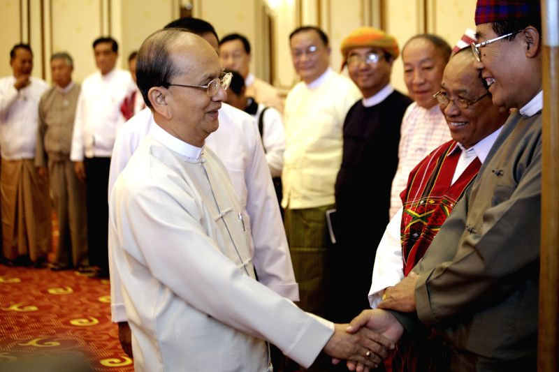 Myanmar President U Thein Sein (L) greets representatives of ethnic parties and regional ethnic affairs ministers before the meeting with leaders of political ..