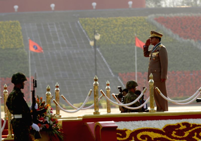 Commander-in-Chief of Myanmar's Defense Services Senior-General Min Aung Hlaing (1st R) salutes the national flag during a military parade to mark the 70th ...