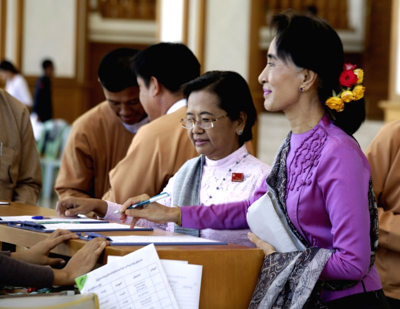 Nay Pyi Taw (Myanmar): Aung San Suu Kyi (R), leader of Myanmar's National League for Democracy (NLD), signs registration forms to attend the 11th regular session of the Union Parliament in Nay Pyi ...