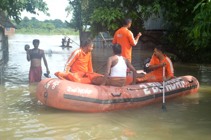 NDRF personnel carry out rescue operation at a flooded village near Alipurduar of West Bengal on July 26, 2016.