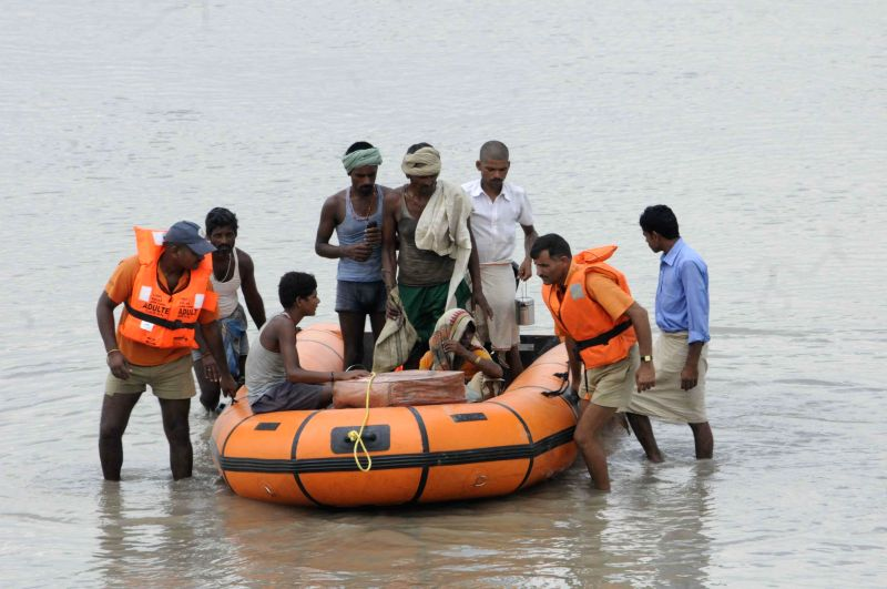 NDRF personnel rescue villagers to higher lands near Indo- Nepal border at Birpur in wake of Kosi flood alerts in Supaul district of Bihar on Aug 3, 2014.