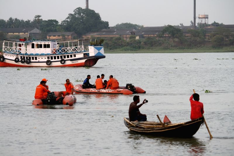 NDRF workers conduct search and rescue operation after a temporary jetty on the Hooghly river collapsed killing at least three persons died in Hooghly district of West Bengal on April 26, ...