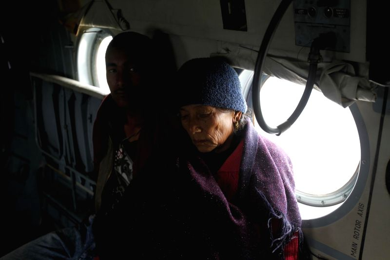 Evacuated mother and son being flown to a safer place by an Indian Air Force (IAF) helicopter yesterday following a recent massive earthquake in Nepal.