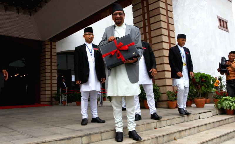 Nepalese Finance Minister Ram Sharan Mahat (front) shows a briefcase containing the budget speech of the fiscal year 2015-2016 before entering the parliament in ... - Ram Sharan Mahat