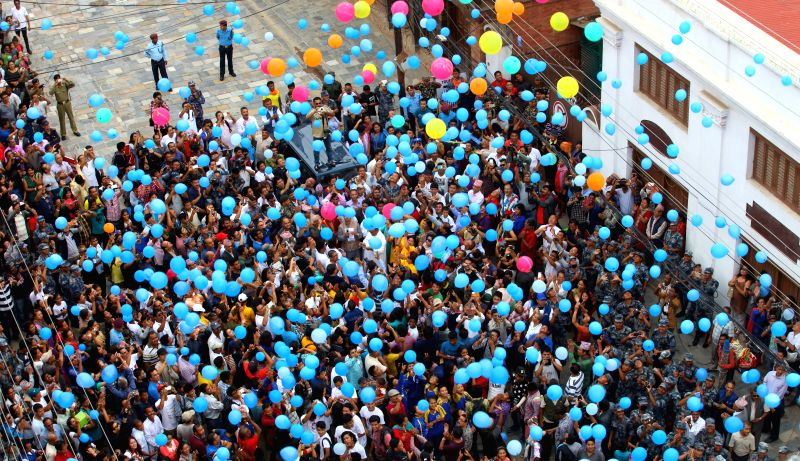 Nepalese people release balloons in memory of the victims of the deadly April 25 earthquake during a memorial procession near the damaged Basantapur Durbar Square ...