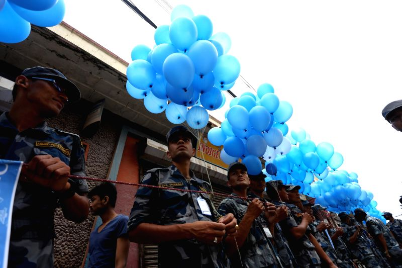 Nepalese police personnel gather to release balloons in memory of the victims of the deadly April 25 earthquake during a memorial procession near the damaged ...