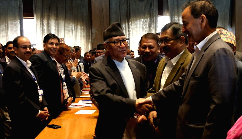 Nepali Congress leader Kul Bahadur Gurung (C) shakes hands with a leader filing his nomination for the election of President at Parliament in Kathmandu, Nepal, ...