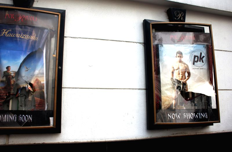 A broken poster frame  at a Delhi theatre screening Amir Khan starrer `PK`  in New Delhi, on Dec 28, 2014. Some people staged a protest against the film at the theatre. - Khan