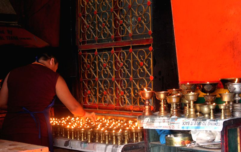 A Buddhist monk lights lamps at a temple on Buddha Purnima in New Delhi, on May 4, 2015.